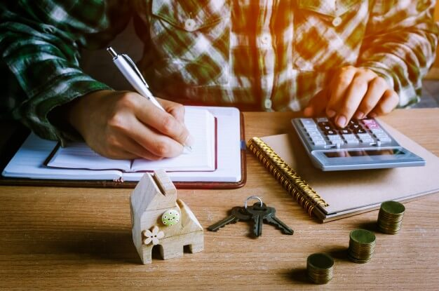 homem escrevendo em um caderno com uma caneta e fazendo contas em uma calculadora