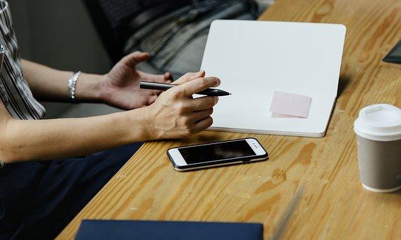 mãos de uma profissional segurando uma caneta e fazendo anotações em um caderno