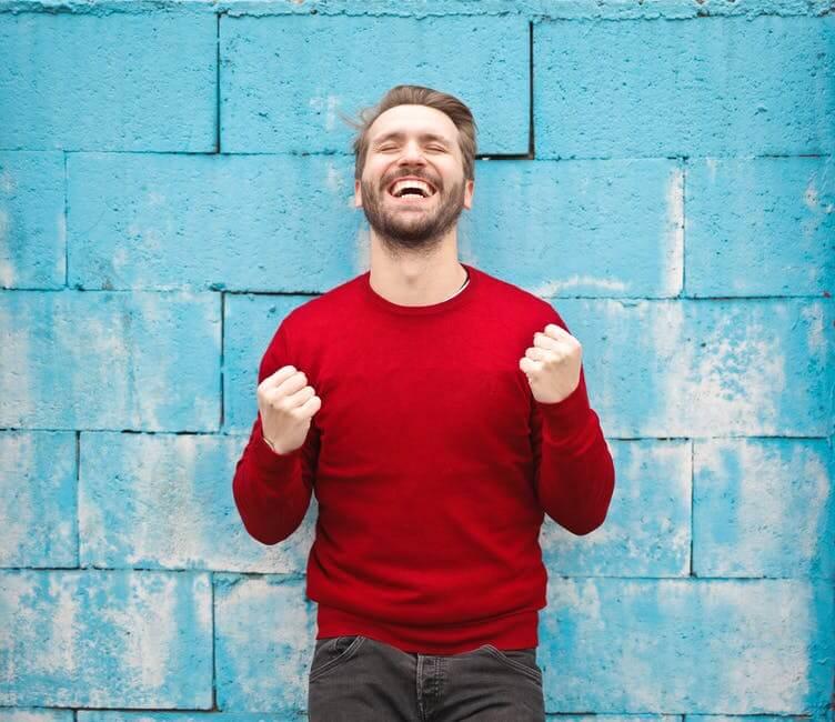 homem comemorando e sorrindo de blusa vermelha em frente uma parede azul