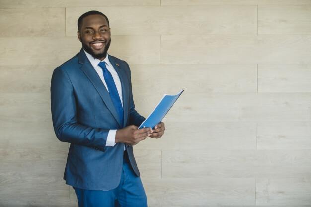 homem de terno sorrindo e segurando um currículo