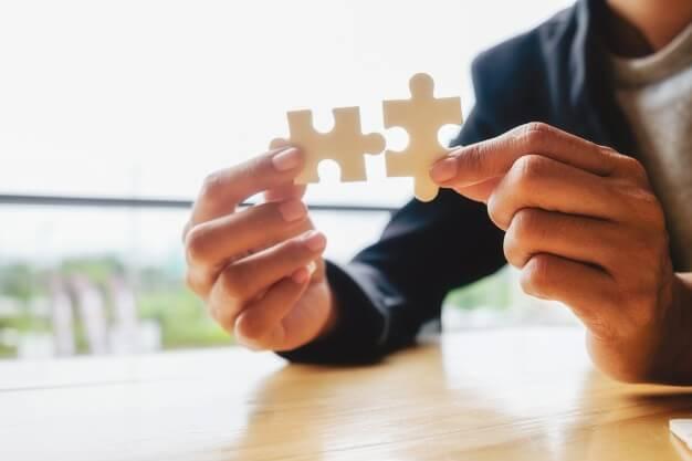 mãos encaixando peças de quebra-cabeça
