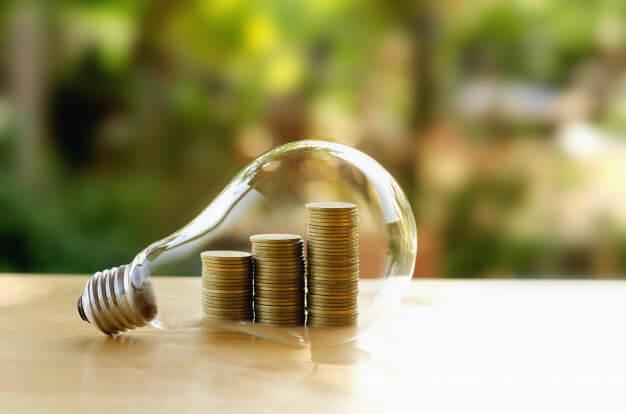 lâmpada de vidro com moedas dentro representando organização financeira