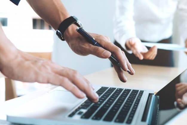 mãos de homem segurando uma caneta e usando o notebook