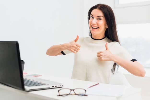 mulher em frente a um notebook sorrindo e fazendo sinal de positivo com as duas mãos