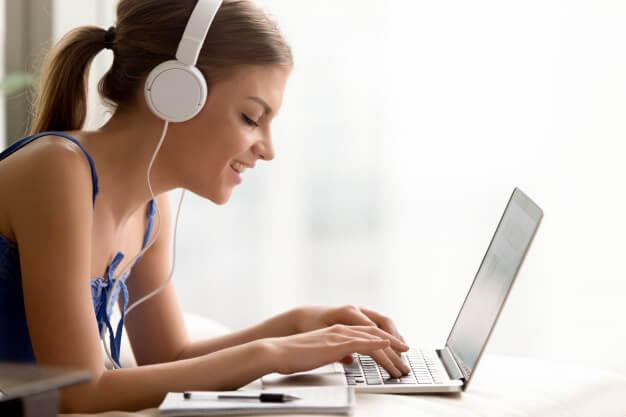 menina fazendo cursos extracurriculares online com fone de ouvido