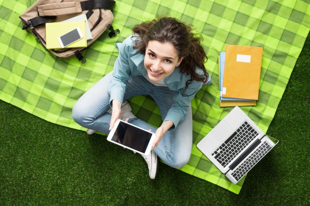 Menina sentada em área verde, com seu notebook, tablet e cadernos para estudo.