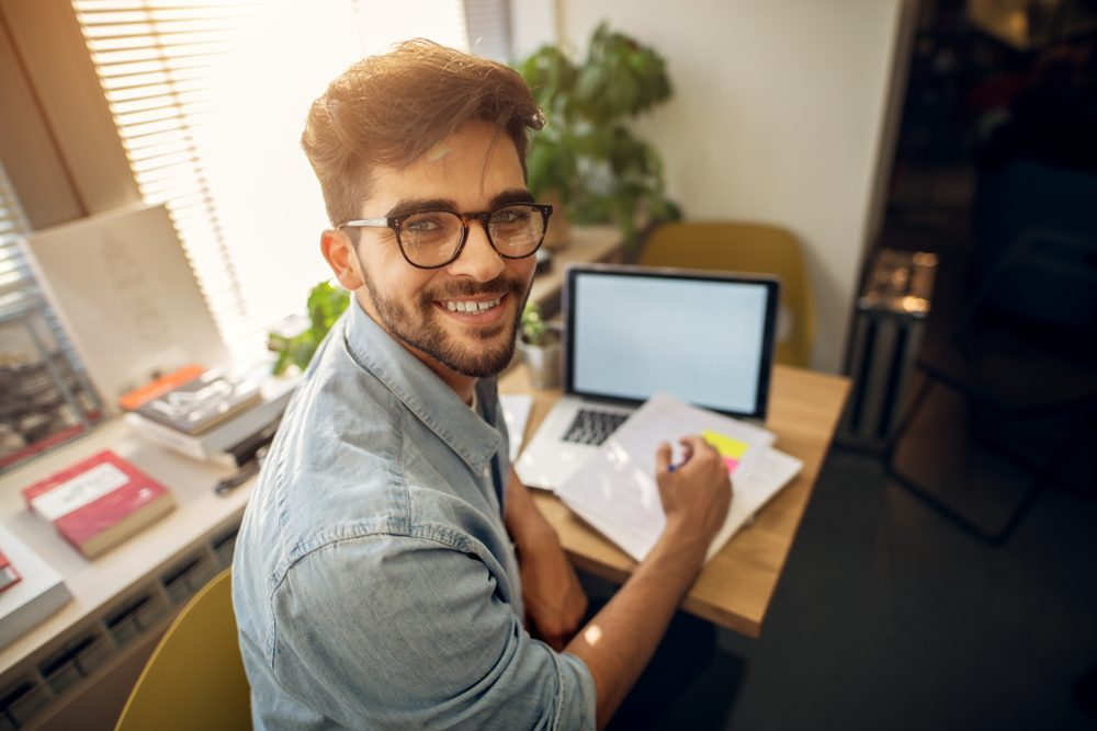 A imagem mostra um rapaz, sentando em uma mesa de estudos, com um notebook e papéis, sorrindo para a câmera