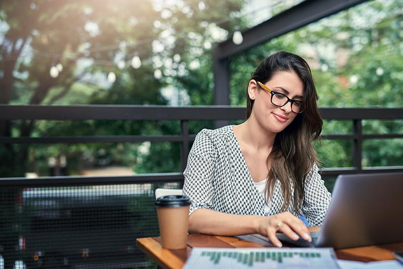 Imagem mostra mulher trabalhando em uma mesa em ambiente externo, com um computador à frente e um café