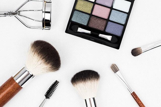 Na imagem, há vários pinceis de maquiagem e uma sombra