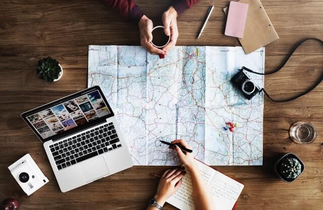 Pessoas olhando mapa sobre a mesa com notebook