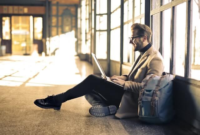 Homem sentado no chão fazendo curso online