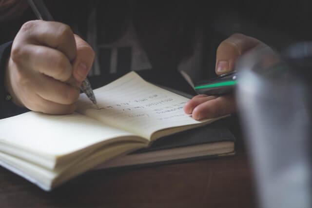 Imagem focada na mão de uma pessoa escrevendo em caderno