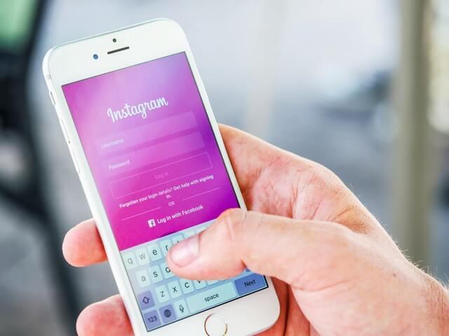 Pessoa segurando um celular com a tela no aplicativo do Instagram