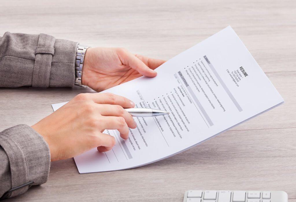 Recrutadora segurando currículo em folha de papel