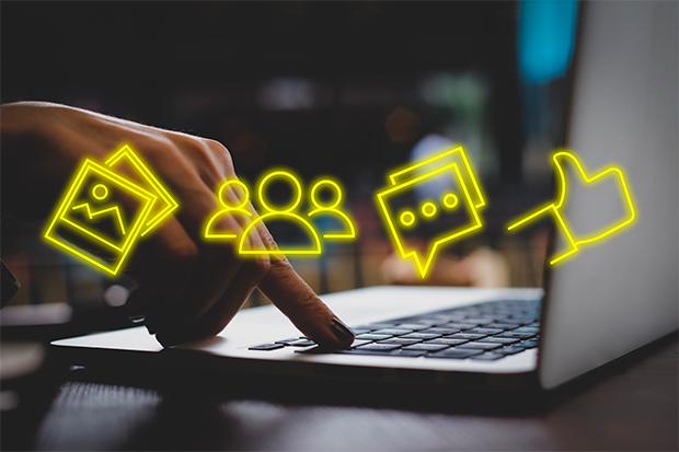 mulher utiizando laptop com vários símbolos sinalizando redes sociais